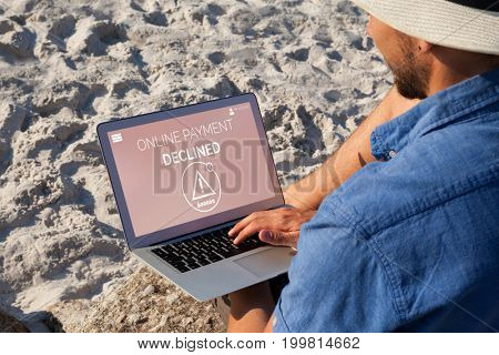 Online payment text on display against man using laptop on the beach