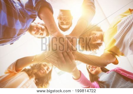 Low angle view of smiling executives forming hands stack at office
