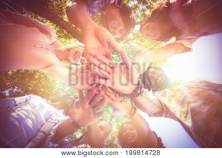 Low angle view of smiling friends forming hands stack