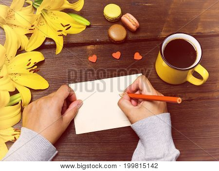 Female hands with a red pencil near a white blank postcard on a brown wooden table next to a cup of coffee
