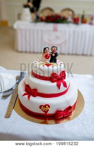 Wedding Cake With Red Ribbons And The Figurine
