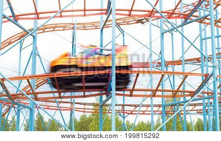 Colorful amusement park ride car going fast by with full speed. People having fun in theme park. Motion blur.