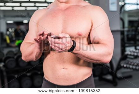 young man using fitness bracelet during sports training in the gym.