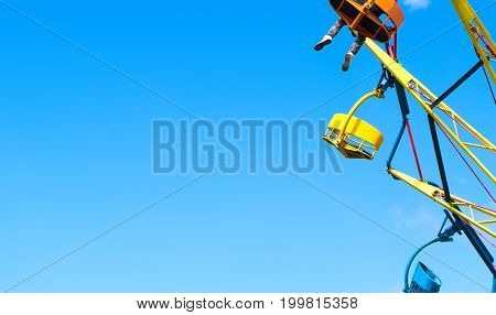 Amusement park background template with negative copy space. Colorful theme park ride against clear blue sky in summer. One person with legs hanging.