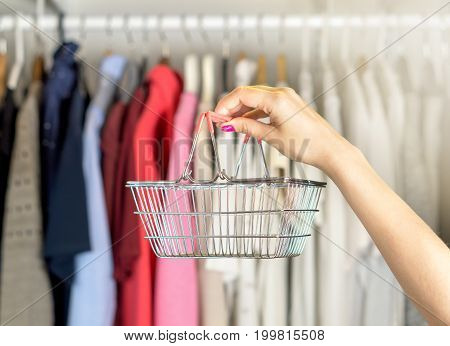 Woman shopping for clothes. Customer holding basket in a fashion store and clothing shop.