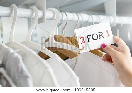 2 for 1 and two for one offer and special deal for t-shirt and clothing in clothes shop. Customer holding price tag with reduced discount price. Bargain and reduced cheap clothing in store.