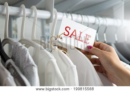 Female customer browsing clothes in a shop or outlet. Woman shopping for fashion offer and deal. Holding price tag with sale text. Bargain and reduced cheap prices in clothing store.