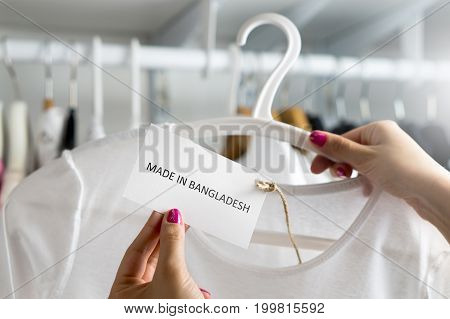 T-shirt made in Bangladesh. Customer looking at the origin and import country of a cheap fashion product in clothes store or shop. Ethical consumer behavior. Woman holding label and price tag with text.
