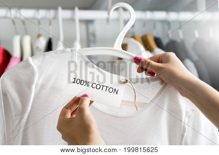 T-shirt made of 100% and hundred percent cotton. Customer looking at the material, fabric and textile of a fashion product in clothes store or shop. Woman holding label and price tag with text.