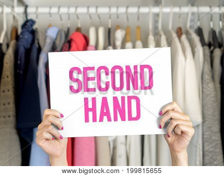 Second hand clothing shop. Used clothes hanging in hanger in a rack and wardrobe in a fashion store with discount and bargain prices. Woman holding advertising and marketing banner in hand.