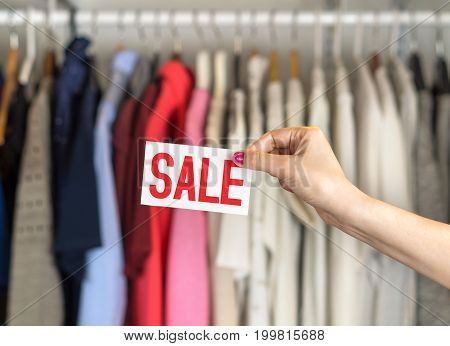 Clothes hanging in hanger in a rack and wardrobe in a fashion store with discount and bargain prices.