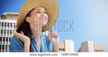 Portrait of beautiful blonde women wearing hat against low angle view of city buildings