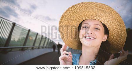 Portrait of beautiful blonde women wearing hat against footbridge against cloudy sky
