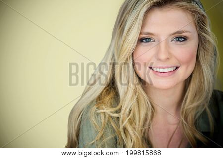 Close up portrait of smiling young blonde woman against light green background