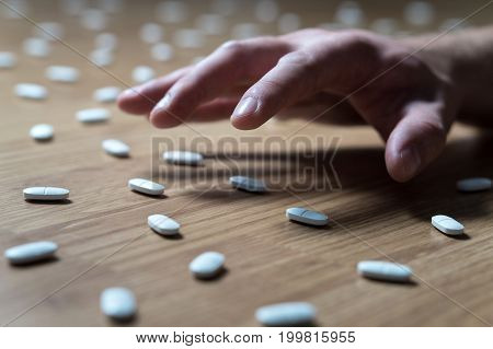 Drug addict with withdrawal symptoms reaching out to many pills on the floor with hand. Drug addiction, medical abuse and narcotics hook and dependence concept. Tablet overdose.