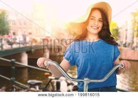 Smiling women riding bicycle  against canal in amsterdam