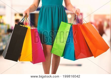 Women holding shopping bag  against interior of modern shopping mall