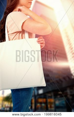 Women holding bag with blank space against skyscraper in city