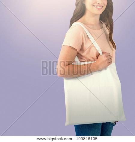 Beautiful brunette women holding bags against purple paper