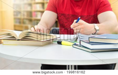 Young athletic man and student studying and writing notes in public or school library in college or university. Stack and pile of books, pen and paper on table.