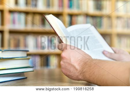 Man or student reading a book in public or school library in college or university. Education, studying and literature service concept. Hands holding book with bookshelf and bookcase in the background