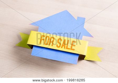 House for sale. Real estate business concept. Selling and buying home. Cottage made from cardboard paper on wooden table.