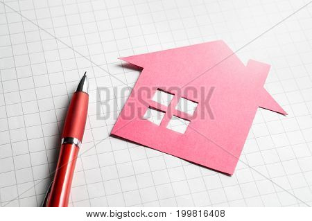 Real estate and selling or buying homes concept. Apartment for sale. Pen, paper and cardboard paper house.