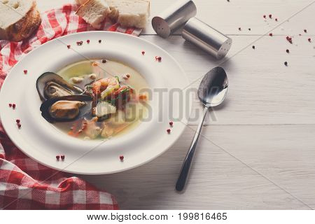 French cuisine restaurant. Seafood soup with white fish, shrimps and mussels in plate sprinkled with spices. Freshly cooked exclusive meals on white wood with checkered cloth and cutlery, copy space