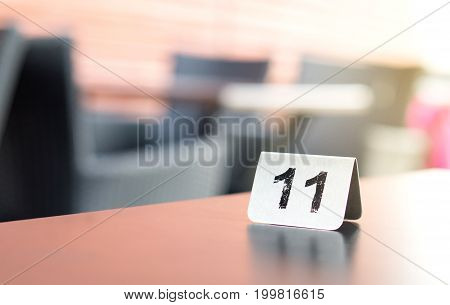 Number sign on restaurant table in outdoor terrace to show reservation. Customer waiting for service or food.