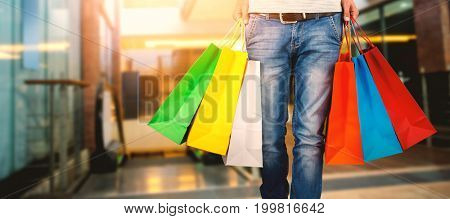 Composite image of low section of man carrying colorful shopping bag