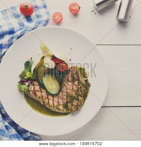 Dining at restaurant. Grilled black angus steak with vegetables and green pepper sauce. Delicious healthy food served on round plate at white wood background and checkered cloth, copy space, top view