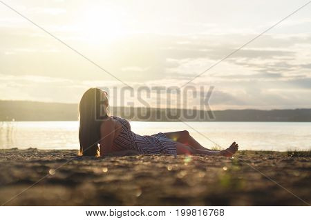 Woman relax and lay down in the sunset on the beach. Carefree and happy lifestyle.