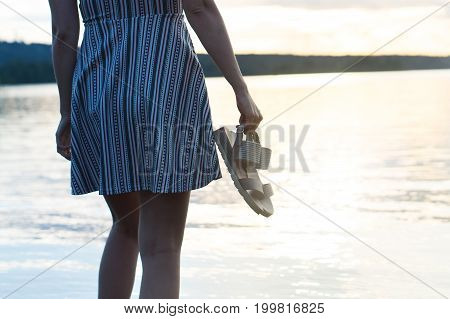 Woman in dress enjoying beautiful sunset on the beach. Freedom and carefree lifestyle. Holding shoes in hand.