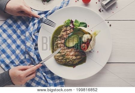 Lunch at restaurant. Grilled black angus steak with steamed vegetables in fennel and green bell pepper sauce. Woman dining at nicely served white wood table with checkered cloth, copy space, top view
