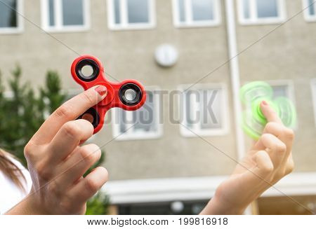 Teenage girl playing with two fidget spinners at recess or break in school yard.