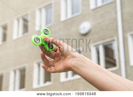Teenage girl playing with fidget spinner at recess or break in school yard.