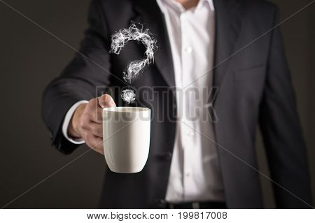 Question mark from coffee steam. Smoke forming a symbol. Business man in a suit holding a hot beverage in a mug and tea cup.