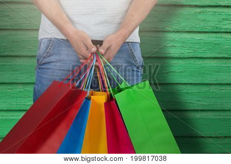 Midsection of man carrying colorful shopping bag against white background against full frame shot of green wall