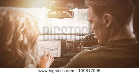 Rear view of couple using tablet computer in car during test drive