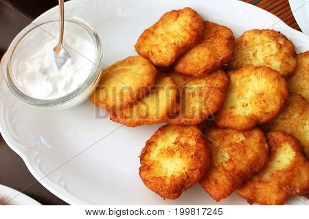 Tasty potato pancakes with sauce on white plate closeup