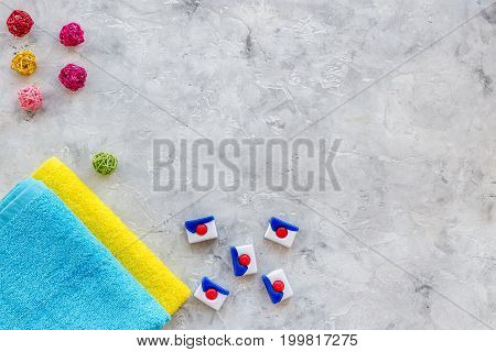 Laundry. Bars of dry detergent near clean towel on grey stone background top view.