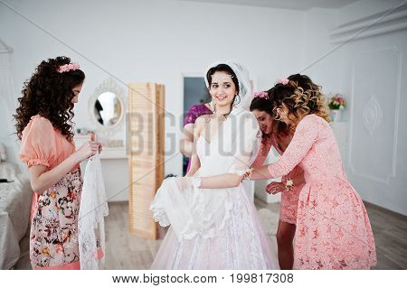 Helpful Bridesmaids And Mother Helping Bride To Tie The Dress Up In Big Light Room.