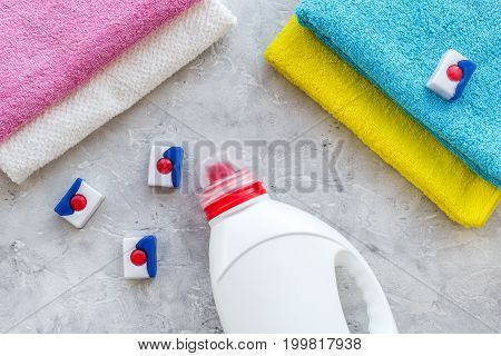 Dry and liquid detergents near clean towel on grey stone background top view.