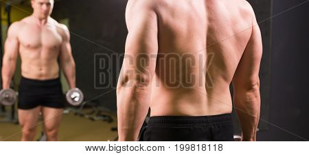 Good looking young man lifting dumbbells and working on his biceps in front of a mirror at the gym