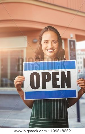 Portrait of female owner with open sign against cafe building exterior on street