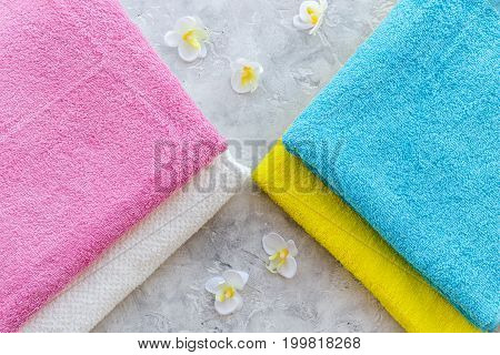 Fresh towel after washing on grey stone background top view.