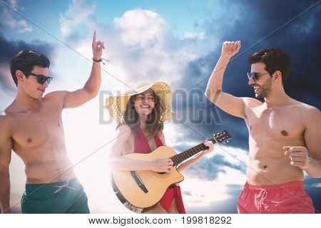 Teenagers dancing and playing music  against cloudy sky