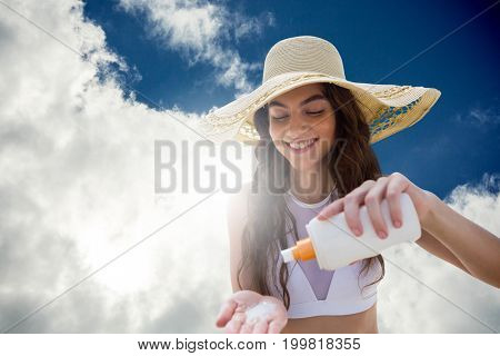 Beautiful women applying suncream and wearing hat against view of beautiful sky and clouds