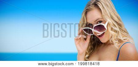 Portrait of young women wearing sunglasses against scenic view of sea against sky