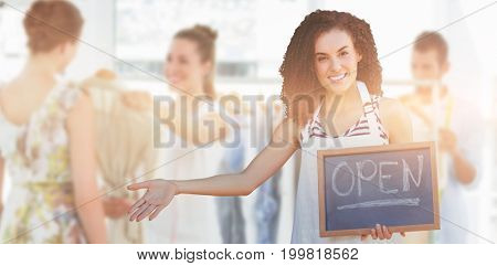 Portrait of young woman holding writing slate with open text against seller helping shopper choose clothes in store
